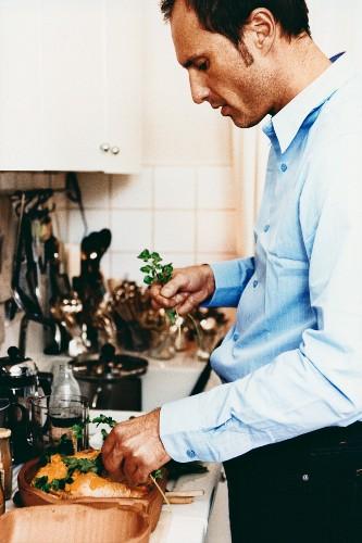 Man putting coriander on chicken in terracotta pot (Romertopf)