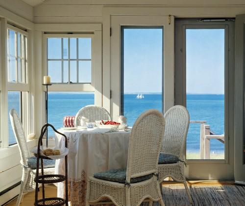Raumecke mit Fenstern und Fenstertüren, mit einem runden Esstisch, Korbstühle und einen weiten Blick aufs Meer
