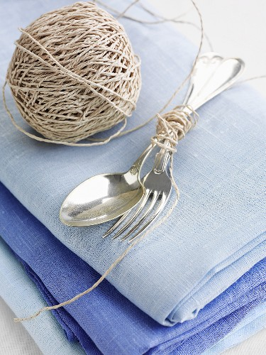 Cutlery tied with kitchen twine on a blue linen cloth