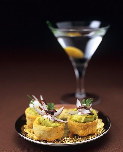 Small guacamole tarts, glass of Martini