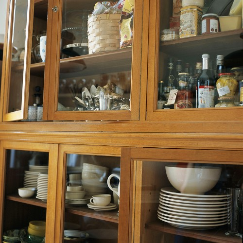 Crockery and groceries in kitchen cupboard