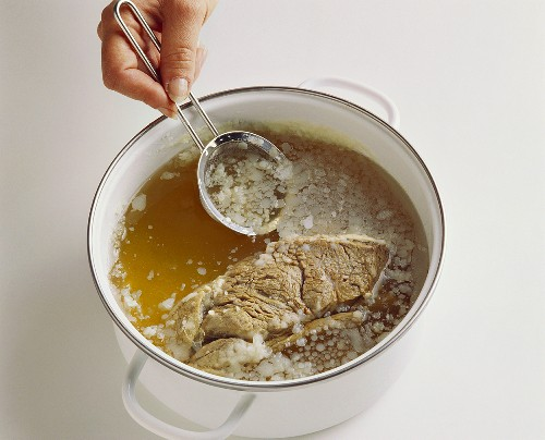 Removing the fat from cold beef stock with a sieve