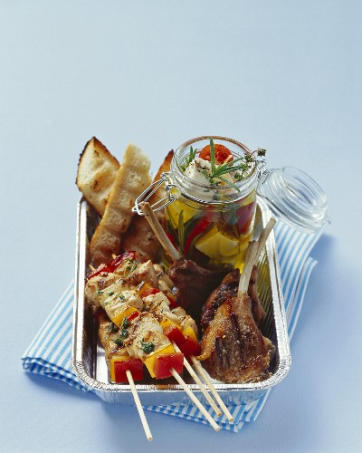 Kebabs, lamb chops and pickled cheese in aluminium dish