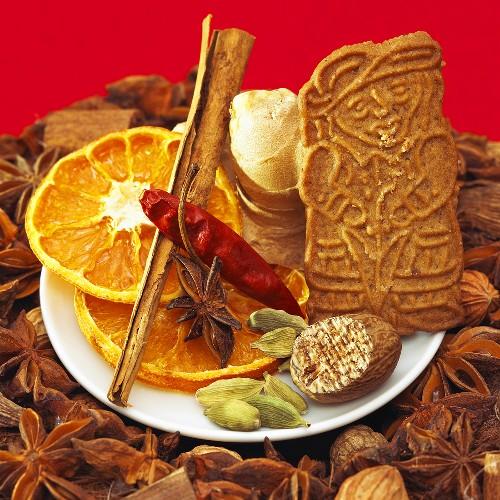 Christmas spices, dried orange slices & spekulatius cookie on plate