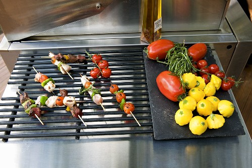 Kebabs on a grill rack and vegetables