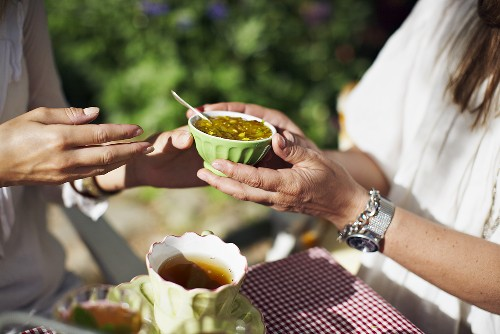 Afternoon tea in the garden: a woman holding a bowl of jam