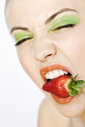 Young woman with a strawberry in her mouth