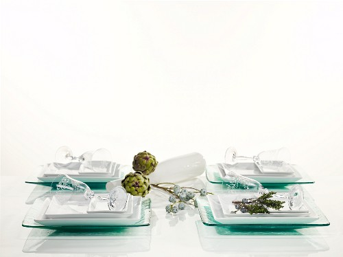 A simply laid table for four people with glass plates and decorative vegetables