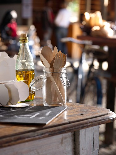 A preserving jar being used as a cutlery holder on a table