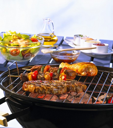 Grilled meat on the barbeque with marinade, salad and sauces in the background