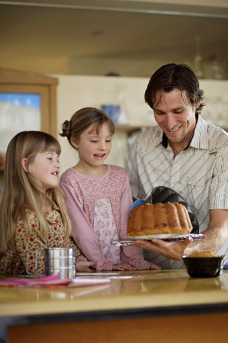 Father showing daughters how to turn a cake out of the tin