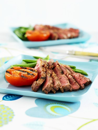 Sliced beefsteak with grilled tomato and green beans