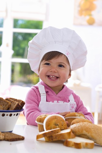Little girl in chef's hat sitting at table with muffins