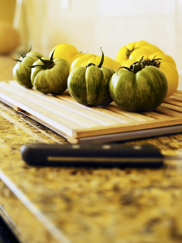 Green and yellow tomatoes on chopping board