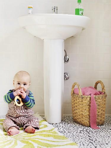 Baby sitting on rug in bathroom