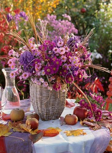 Arrangement of Michaelmas daisies, apples, autumn leaves on table