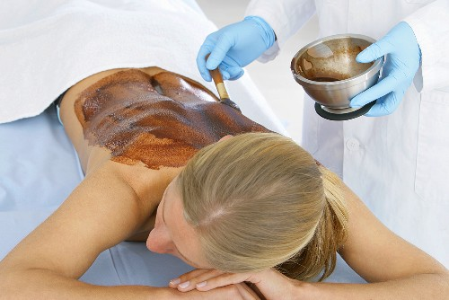 Applying a chocolate mask to someone's back