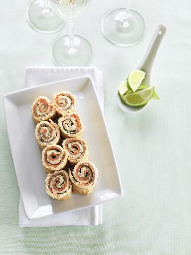 Pfannkuchenröllchen mit Räucherlachs und Limettenschnitze