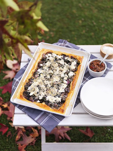 Chard, olive and onion tart on a garden table