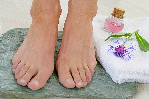 Someone's feet on a stone, towel, cosmetic bottle