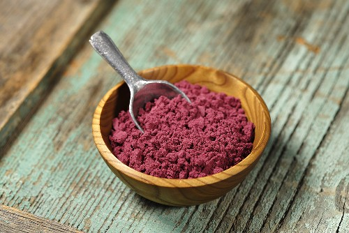 Acai powder (diet aid) in small wooden bowl with scoop