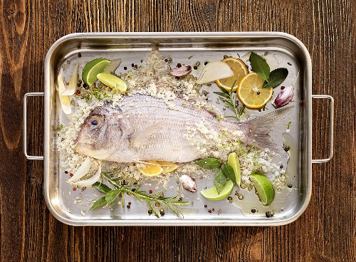 Bream with sea salt and spices in a roasting tin