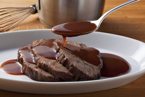Roast beef being served with gravy