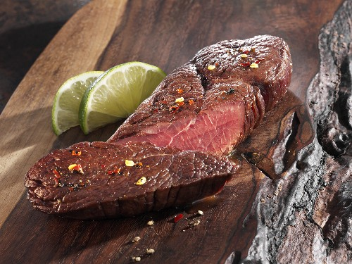 Roasted ostrich fillet on a wooden board