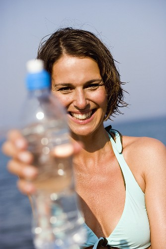 Woman with a bottle of mineral water on the beach
