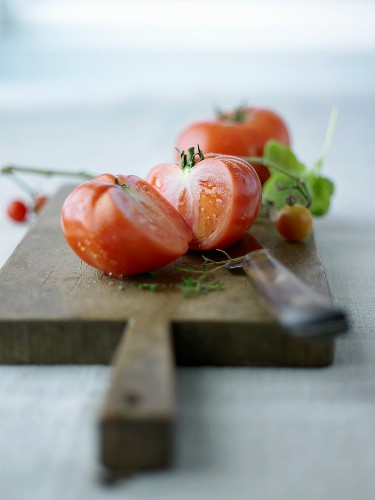 Whole and halved beefsteak tomato on a chopping board