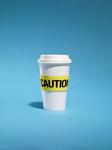 Cup of coffee with warning sign