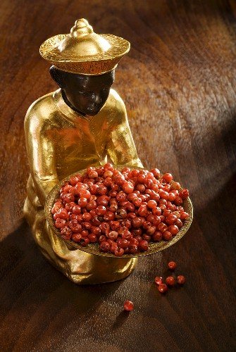 Gilded statuette with a bowl of red pepper
