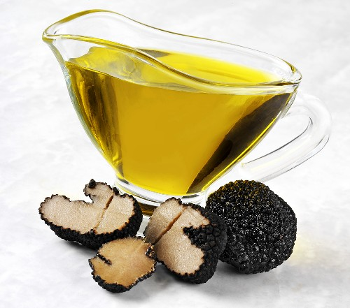 Truffle oil in a small jug, summer truffles in front