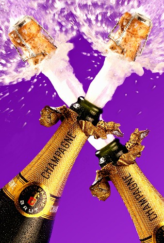 Corks flying out of two champagne bottles