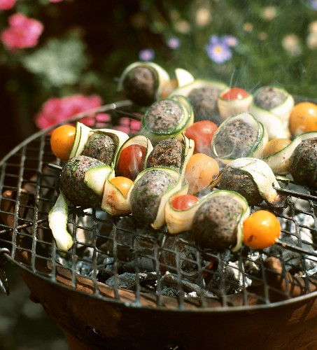 Kebabs with black bean paste, cherry tomatoes and courgette