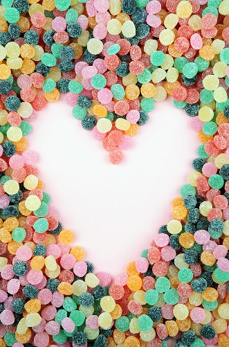 Bonbons creating a heart in the negative space