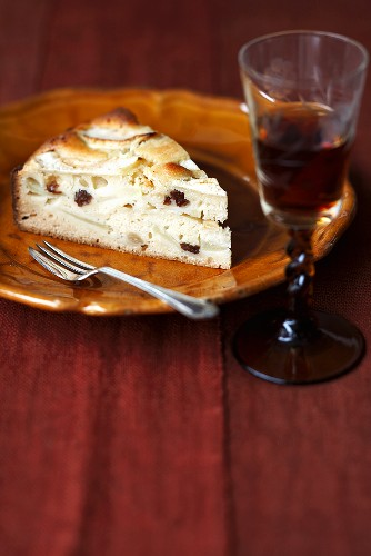 A slice of apple cake with a glass of liqueur