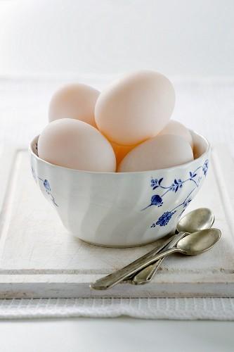 Duck eggs in ceramic bowl, spoons