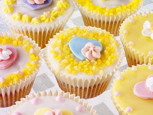 Pastel-coloured fairy cakes with sugar flowers