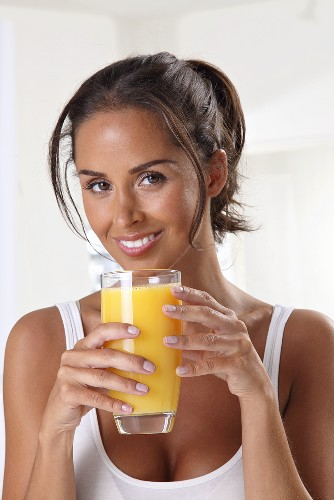 An athletic woman holding a glass of orange juice
