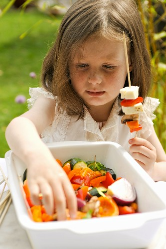A girl preparing vegetable kebabs for the barbeque