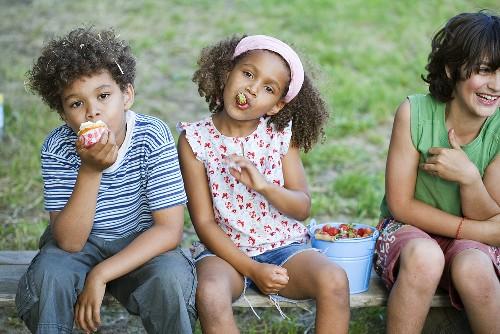Kinder essen Erdbeeren und Muffin