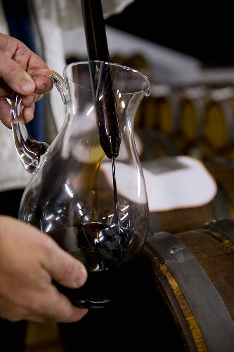 Balsamic vinegar being poured into a glass jug