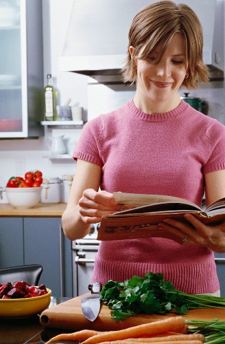 Woman in kitchen reading recipe