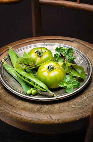 Dish of green tomatoes, peas, basil, lettuce and beetroot leaves
