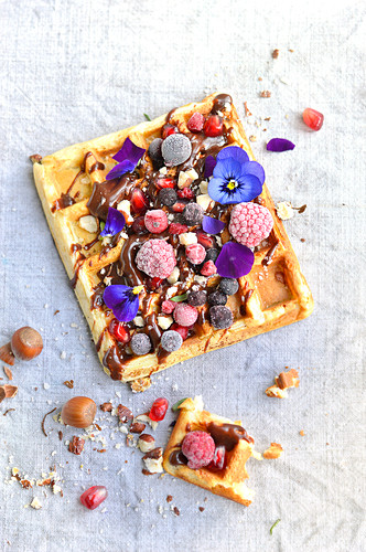 Waffle with fresh fruit, dried fruit, flowers and chocolate sauce