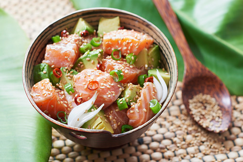 Salmon and avocado poke with peppers and sesame seeds
