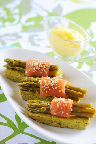Asparagus flan topped with bundles of asparagus with salmon and sesame seeds,mousseline sauce