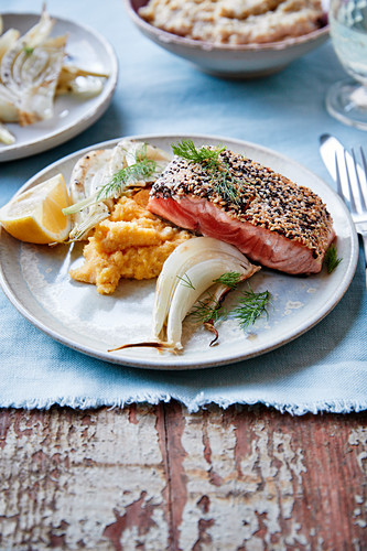 Piece of half-cooked salmon with black and golden sesame seeds,pumpkin mash,fennel and dill