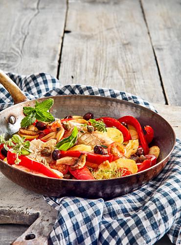 Sautierter Seehecht mit Kartoffeln, Paprika und Champignons in der Pfanne